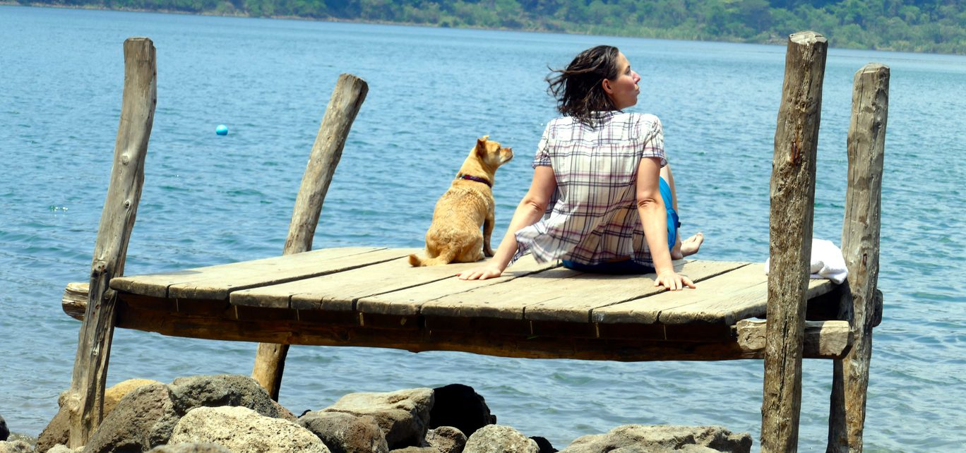 Lady and dog sitting near the lake distracted by something